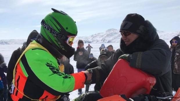 Bobby Gordon (left) shakes hands with Jordan Akavak Flaherty in Kimmirut, at the halfway point of the race. Racers give a traditional handshake to a Kimmirut local before returning to the finish line, in Iqaluit.