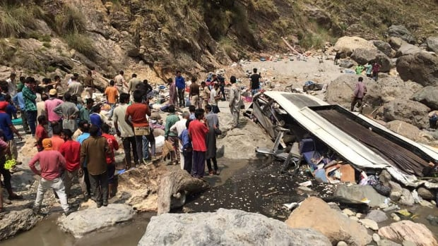 Indian rescue personnel and volunteers stand amid wreckage and victims after a bus accident, at the bottom of a ravine near the Tons river.