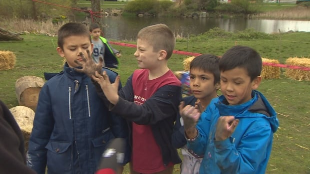 A group of grade schoolers examine their dirty hands after playing at a pop-up playground near Stanley Park.