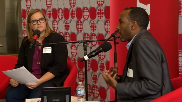 Abdi Ahmed of Immigration Partnership Winnipeg speaks with CBC Information Radio host Marcy Markusa at the CBC Asks town hall.