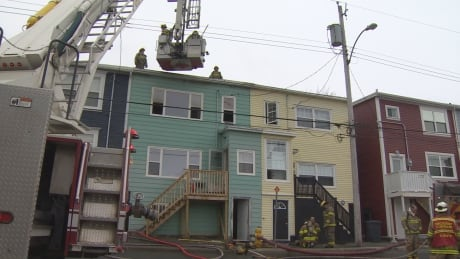 Firefighters check the roof of 52 Monroe St.