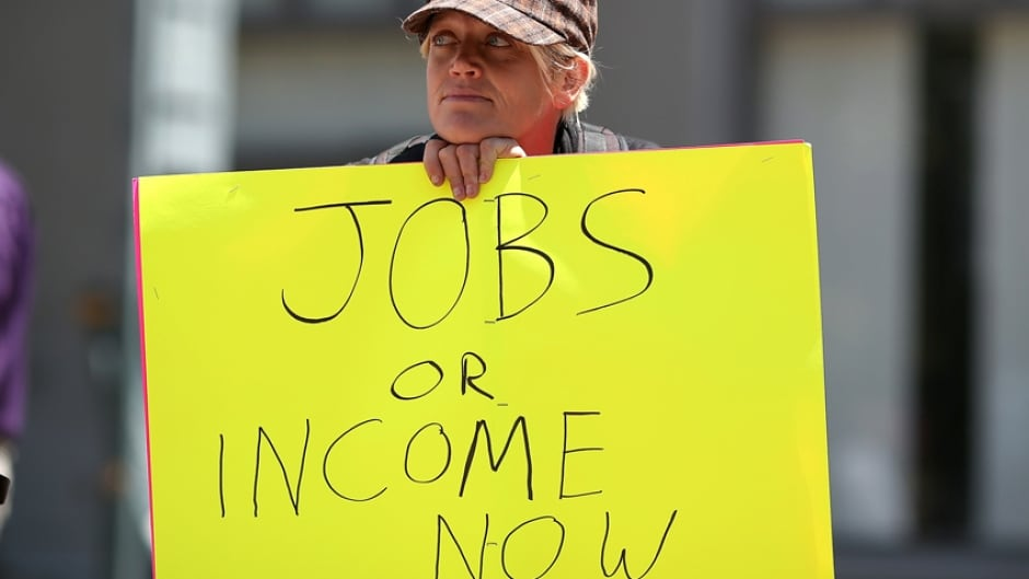 A protester holds a sign during a demonstration against unemployment benefit cuts on July 11, 2012 in Oakland, California.