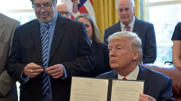 U.S. President Donald Trump shows off the presidential memorandum ordering the Department of Commerce to investigate the national security implications of importing foreign-made steel. Trump lambasted Canada for a second day over what the president says are the country's unfair trade practices.
