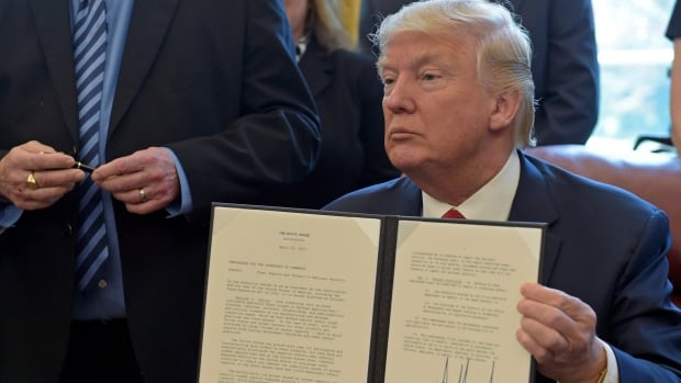 U.S. President Donald Trump shows off a signed executive memorandum on the investigation of steel imports in April at the White House, as United Steelworkers International President Leo W. Gerard looks at the pen used to sign the document.