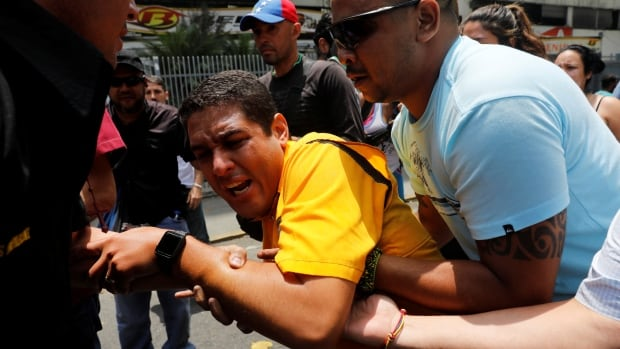 Deputy of the opposition party Justice First Jose Olivares reacts after he was affected by tear gas during a rally against Venezuela's President Nicolas Maduro in Caracas on Thursday.