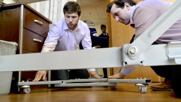 UPEI engineering students show that their prototype will allow mobile stretchers to be moved closer to a patient's bed.