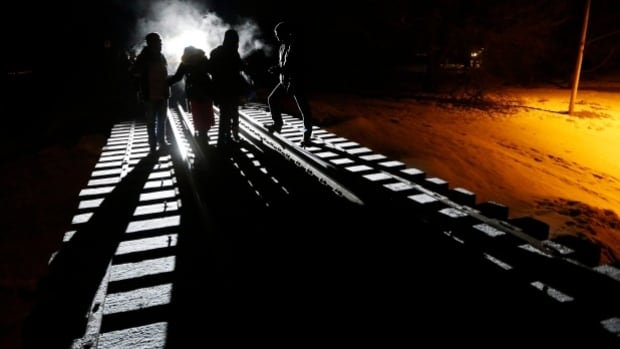 Asylum seekers walk up the rail tracks leading from the U.S. into Canada near Emerson, Man.