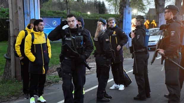 Dortmund's Marcel Schmelzer, third from right, talks to police officers outside the team bus after it was damaged in an explosion before the Champions League quarter-final soccer match between Borussia Dortmund and AS Monaco in Dortmund, western Germany on April 11.