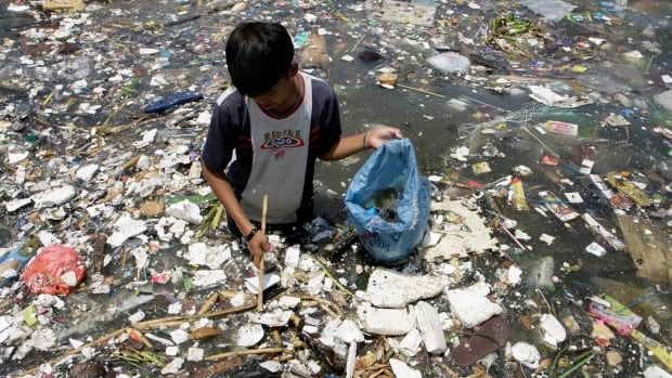 A boy collects plastic materials near a polluted coastline in Manila, Philippines. The plastic found in the Arctic comes up the Atlantic Ocean from as far away as the eastern coast of North America and the northwestern coast of Europe.
