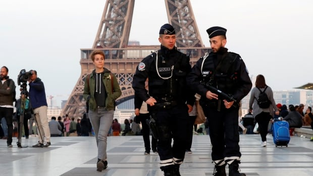 The Eiffel Tower is visible in the background as French police officers patrol in Paris following the attack that killed one police officer and seriously wounded two others. The gunman was also killed and a female tourist was wounded.