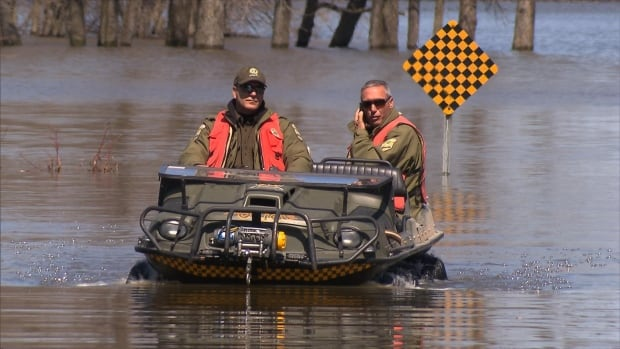 Members of the Quebec provincial police patrol the flood waters in Rigaud, Que., on Monday as a state of emergency continues.