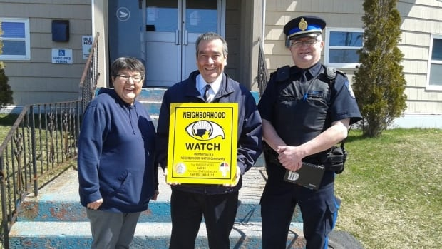 Connie Osborne, Troy Paul and Sgt. Graham Smith (left to right) hold their newly designed neighbourhood watch sign.