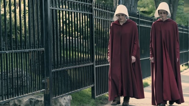 """Offred (Elisabeth Moss) and Ofglen (Alexis Bledel) walk together in Episode 101, """"Offred."""" The handmaids' flowing red dresses have become symbolic of womanhood."""