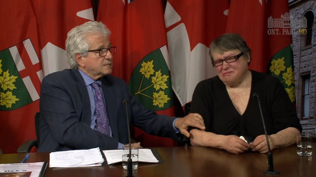 Ontario MPP Mike Colle comforts Wendy Soczek Wednesday. In May 2010, her husband sprayed her with gasoline and lit her on fire. Her insurance company denied her claim.