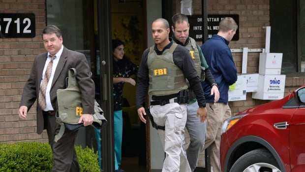 FBI agents leave the office of Dr. Fakhruddin Attar at the Burhani Clinic in Livonia, Mich., on April 21, 2017 after completing a search for documents. A federal judge in Detroit has dismissed one charge against Attar and Dr. Jumana Nagarwala in connection with a female genital mutilation case.