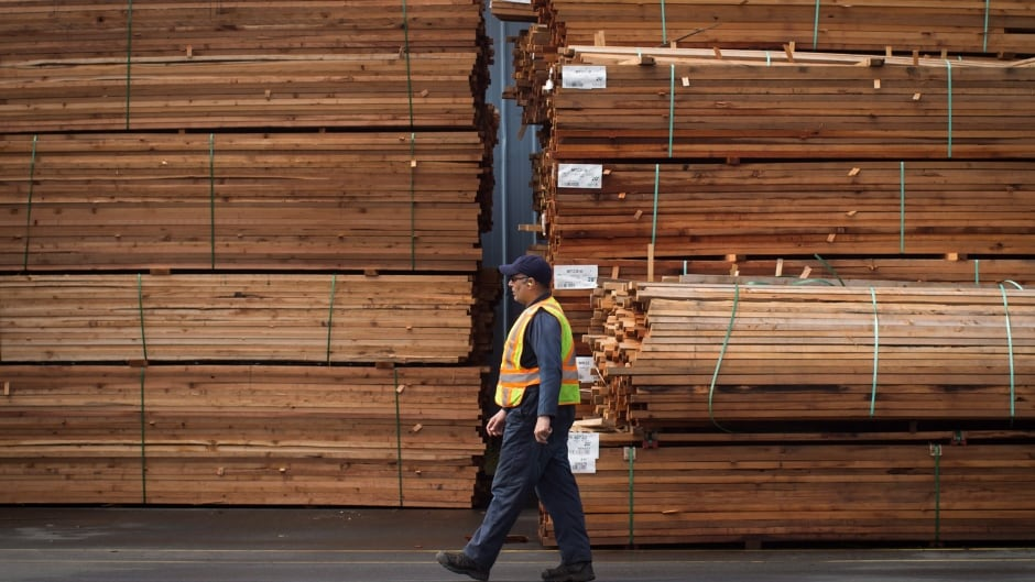A worker walks past stacks of lumber at the Partap Forest Products mill in Maple Ridge, B.C., on Tuesday April 25, 2017.