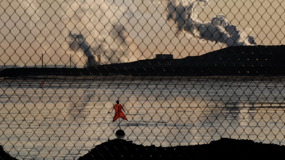 A scarecrow lies in a tailings pond in front of the Suncor oil sands extraction facility near the town of Fort McMurray in Alberta.