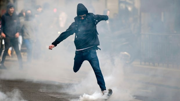 A man kicks back a tear gas canister at police in Paris on April 27, 2017 during a demonstration against the results of the first round of the presidential election.