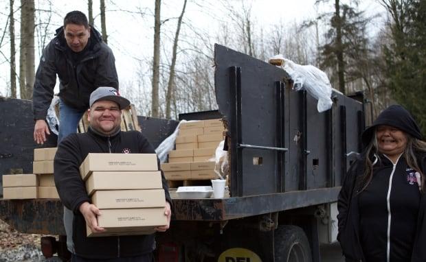 Squamish Nation volunteers unload salmon