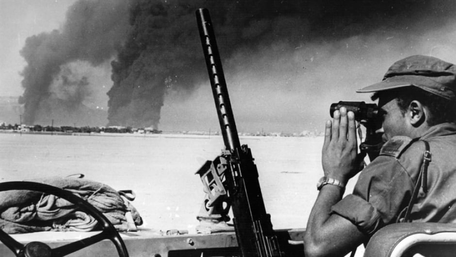 An Israeli soldier studies an oil refinery at Port Suez set alight by Israeli shelling during the Six-Day War. He views it from the other side of the Suez Canal.