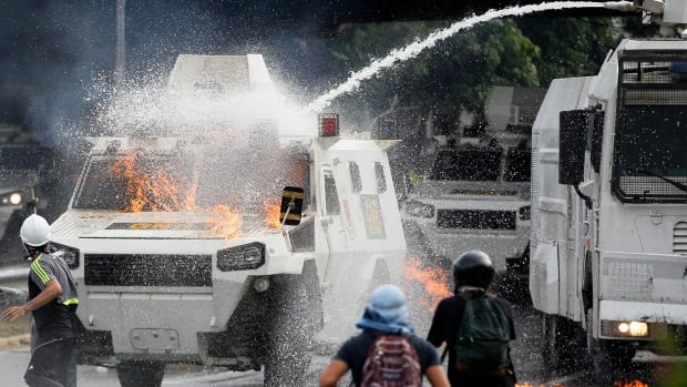 A Venezuelan National Guard water cannon puts out a gasoline bomb that fell on an armoured vehicle during an opposition march in Caracas on Monday. An intensifying protest movement entered  its second month with duelling anti- and pro-government May Day demonstrations.
