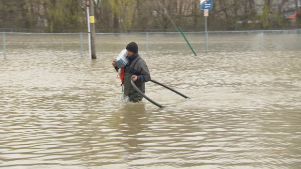 A Pointe Gatineau man wades through floodwaters carrying a sump pump to his home.