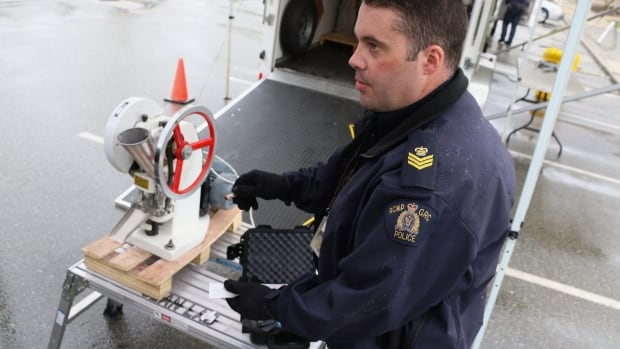RCMP Sgt. Eric Boechler holds a naloxone injection kit, used to reverse opioid overdoses. Behind him, a confiscated pill press sits, ready for a pill pressing demonstration.