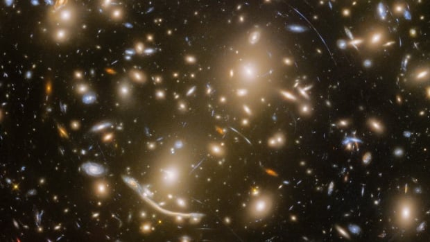Abell 370 is one of the first galaxy clusters in which astronomers observed gravitational lensing, the warping of space-time by the cluster's gravitational field that distorts the light from galaxies far behind it. Arcs and streaks in the picture are the stretched images of background galaxies.