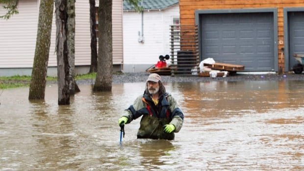A resident walks through the flooded streets of Île Mercier, in Montreal's west end. Mayor Denis Coderre declared a state of emergency on Sunday afternoon, which will remain in effect for at least 48 hours.