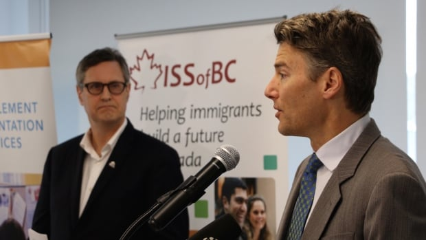 Vancouver Mayor Gregor Robertson (right) speaks at the Immigrant Services Society's welcome centre Wednesday, while ISS director of settlement services Chris Friesen looks on.