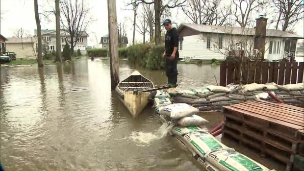 A resident of Île Mercier, in Montreal, stands on the wall of sandbags around his home, watching water levels continue to rise.