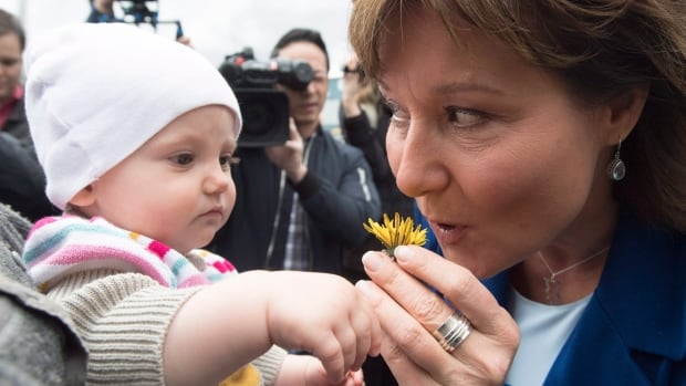 Clark stops to smell a flower given to her by a little girl in Campbell River, B.C., during the provincial election campaign.