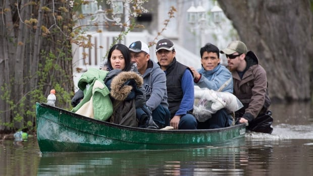 Members of a family are helped into a canoe after being evacuated from their home in the Montreal borough of Pierrefonds on Sunday.