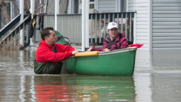 Julie Theriault (right) and Jean-Francois Perrault push a canoe with a neighbour's belongings as they help in the flooded area of Gatineau, Que., on May 7.