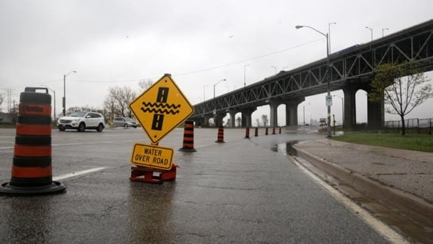 """A photograph taken during a heavy rainstorm earlier this month shows """"water over road"""" signs Eastport Drive. Warnings of possible flooding were issued Thursday."""