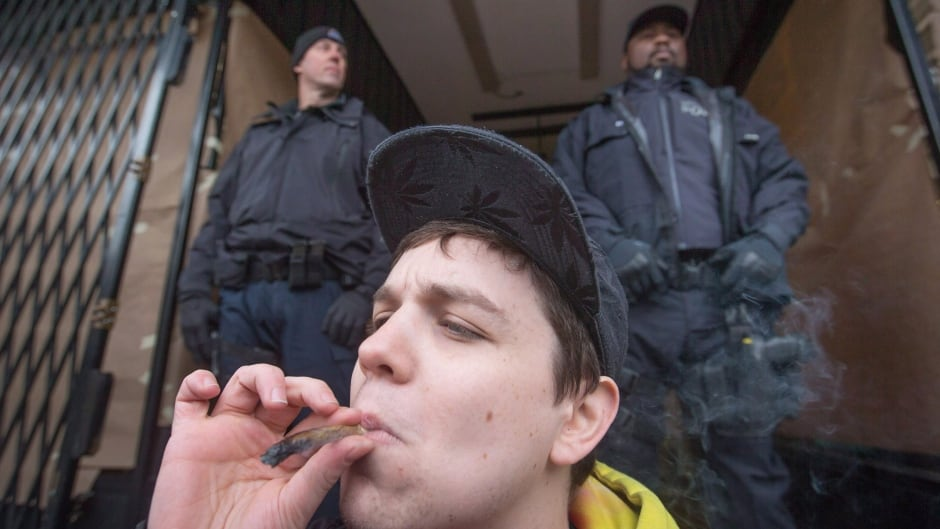 A young man smokes a joint as police officers stand outside the Cannabis Culture shop during a police raid in Vancouver, B.C. on Thursday March 9, 2017. THE CANADIAN PRESS/Darryl Dyck