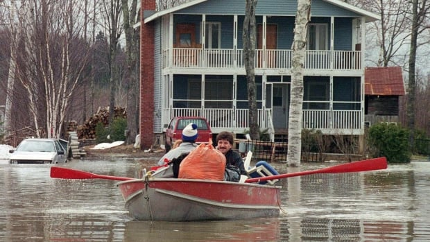 A family from Ayer's Cliff returns home to stock up on food and clothing on April 17, 1994. This flood, one of 36 major inundations in 90 years in Quebec, displaced about 900 families.