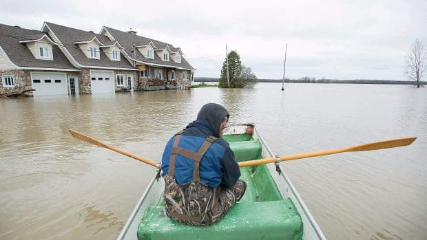 Francois Lussier rows a small boat along a flooded street in the town of Rigaud, Que., west of Montreal on Monday, May 8, 2017, following flooding in the region.