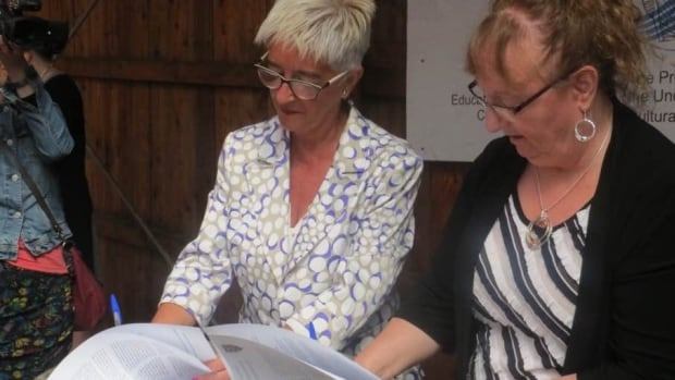 Red Bay Mayor Wanita Stone, right, and Pasaia Mayor Izaskun Gomez  sign the twinning agreement aboard the replica of the Basque whaling boat San Juan.