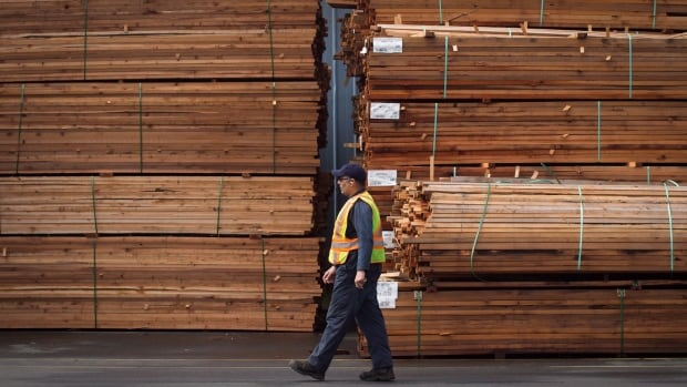 A worker walks past stacks of lumber at the Partap Forest Products mill in Maple Ridge, B.C., in April. The U.S. Commerce Department announced anti-dumping duties for Canadian softwood lumber Monday.