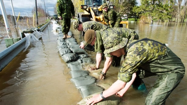 Canadian forces soldiers lay down sandbags to reinforce the highway in Saint-Andre-d'Argenteuil, Que.