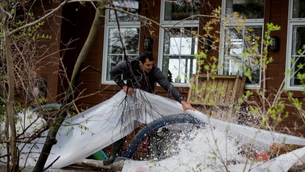 A man works to pump water from his home in a flooded neighbourhood in Deux-Montagnes, Que., May 9, 2017. The Quebec government is compensating those who took measures to protect their homes.
