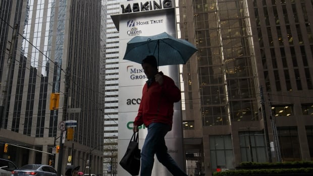 Under a cloud: A pedestrian in Toronto walks past a sign for Home Trust, a subsidiary of Home Capital Group, which has delayed its results till today following a crash in its shares as depositors pulled their cash.