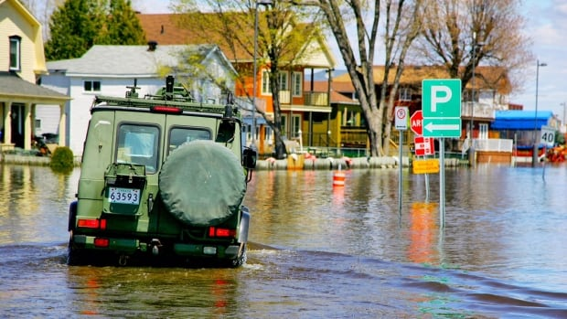 A military vehicle drives down the flooded Jacques Cartier Street in Gatineau, Que. Public Safety Minister Ralph Goodale warned today that flood recovery will not be quick or easy.