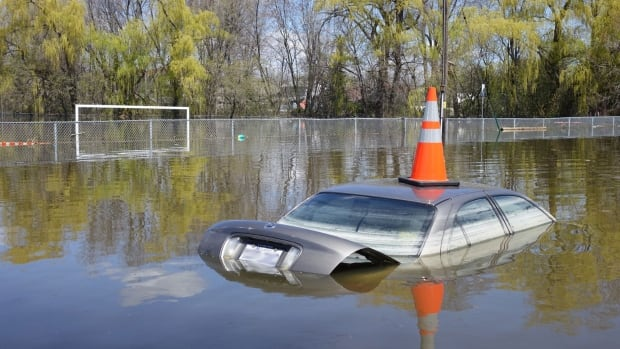 An abandoned parked car sits on flooded Saint-Louis Street in Gatineau's Pointe-Gatineau neighbourhood on Wednesday, two days after water levels peaked.