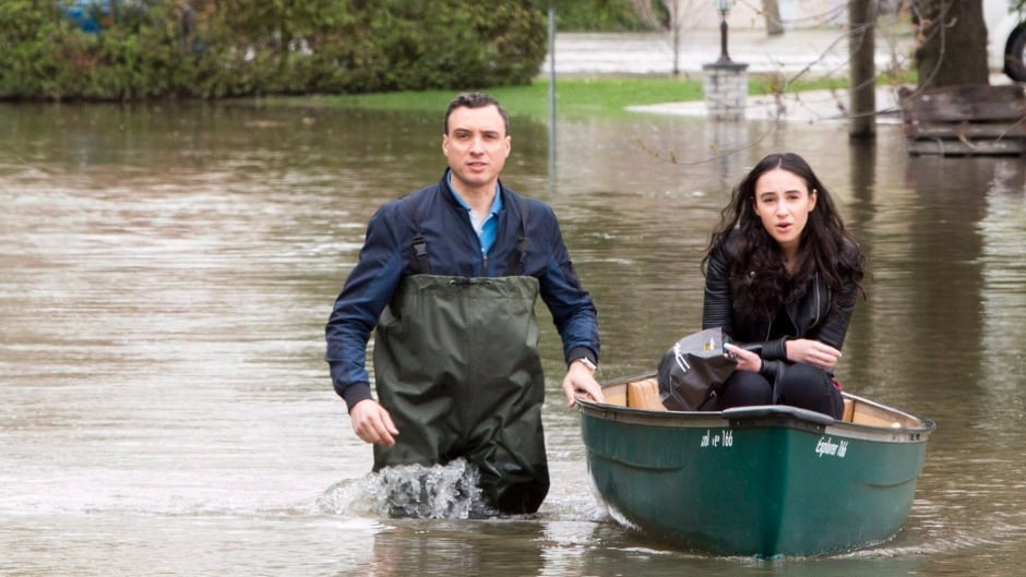 Residents make their way through a flooded streets in Laval, Que.