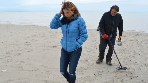 Laura Weyland leads the search for her lost necklace in Long Point, Ont., while Steve Zazulyk follows with a metal detector, on May 10.