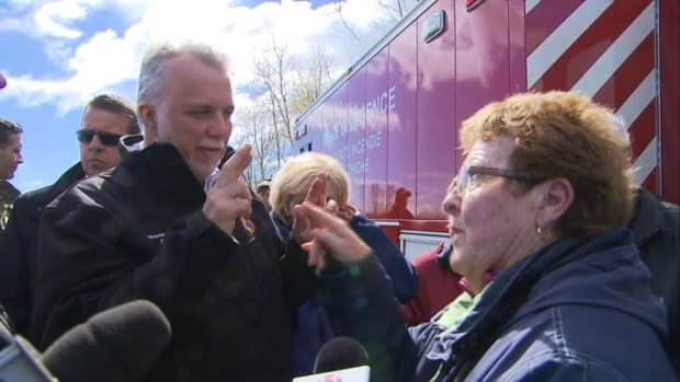 Quebec Premier Philippe Couillard tells a Yamachiche, Que., flood victim that he's crossing his fingers for no more rain.