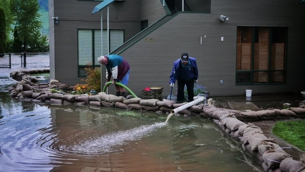 Residents of Holiday Park Resort pump water out from behind a sandbag wall on Thursday night.