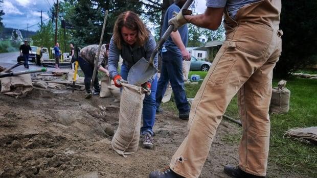 Residents of Holiday Park Resort fill sandbags.